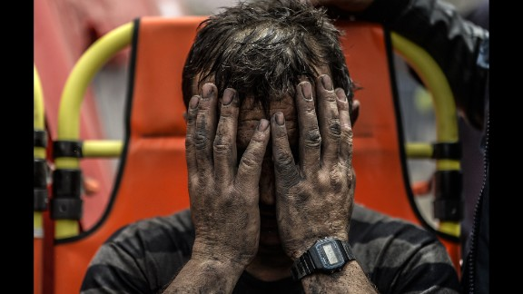 A miner covers his face after being affected by toxic gas during rescue operations on May 14.