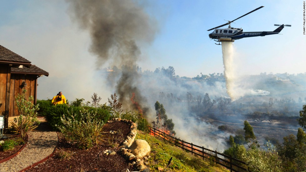 A helicopter drops water near the Rancho Santa Fe neighborhood of San Diego on Tuesday, May 13.