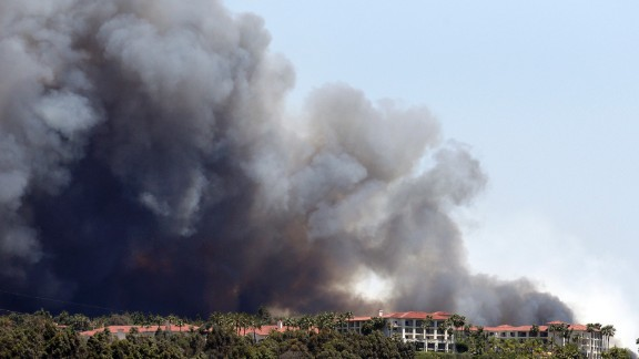 A wildfire approaches buildings in Carlsbad on May 14.