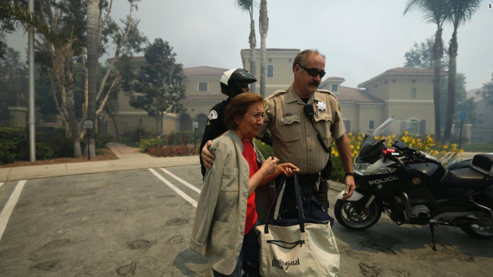 A woman is escorted to safety May 14 in Carlsbad.