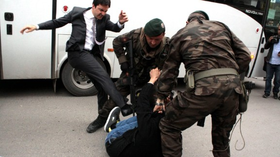 Yusuf Yerkel, an aide to Turkish Prime Minister Recep Tayyip Erdogan, kicks a person who is being wrestled to the ground by two police officers during protests in Manisa, Turkey, on Wednesday, May 14.