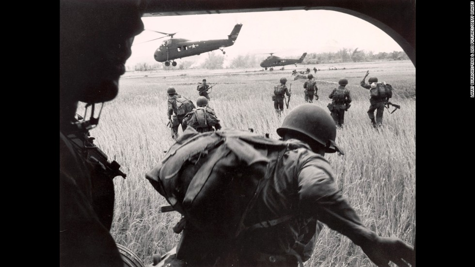 On February 9, 1965, the United States deployed its first combat troops to South Vietnam, significantly escalating its role in the war. Here, the U.S. Marines' 163rd Helicopter Squadron discharges South Vietnamese troops for an assault against the Viet Cong hidden along the tree line in the background.