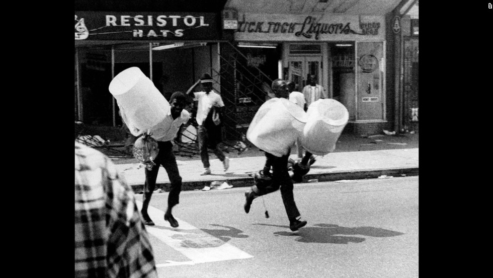 Two youths, carrying lampshades from a looted store, run down a street in the Watts neighborhood of Los Angeles on August 13, 1965. The Watts Riots were sparked by tensions between the city's black residents and police. The six days of violence left 34 dead and resulted in $40 million of property damage.