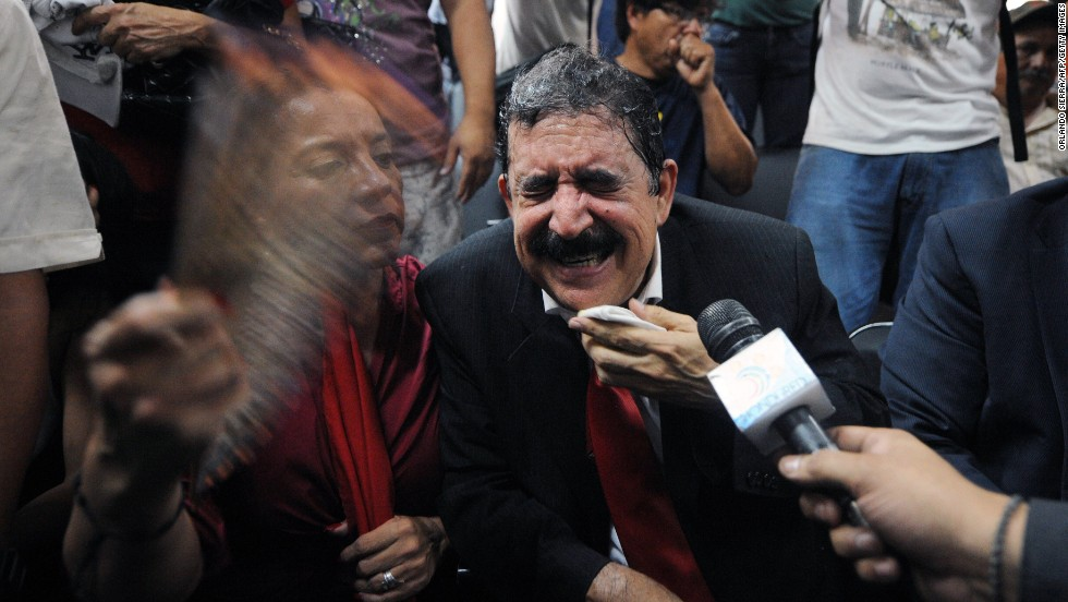 Manuel Zelaya, the former Honduran President who is now a congressman, reacts outside the Congress building after he and other members of his party were tear gassed Tuesday, May 13, in Tegucigalpa, Honduras. Zelaya, his wife and hundreds of supporters clashed with riot police and soldiers after they burst into the Congress building demanding their right to speak.
