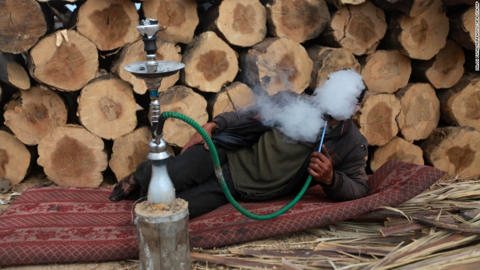 A Palestinian charcoal worker smokes during a tea break at a production facility in Gaza on Monday, May 12.