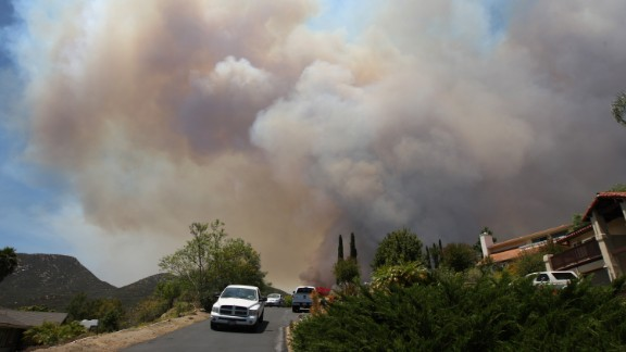 Smoke rises as a wildfire closes in on houses near San Marcos on May 15.