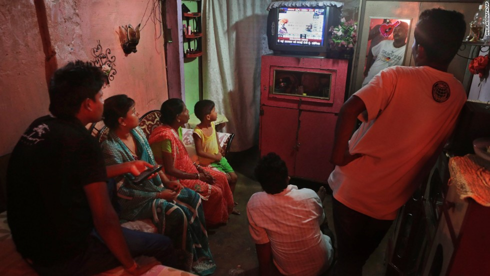 A family follows election results on TV in Guwahati on May 16.