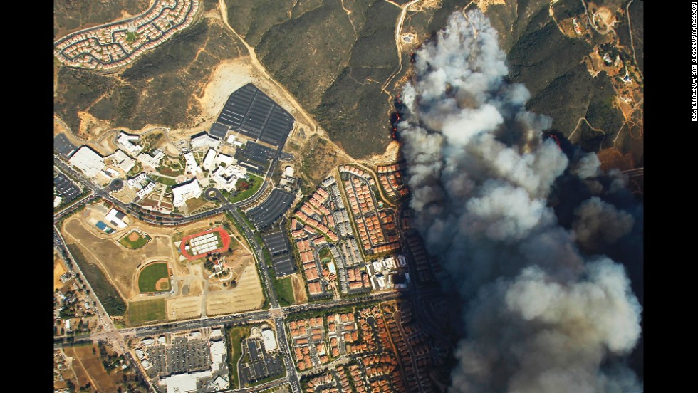 A wildfire burns near homes and California State University in San Marcos on Wednesday, May 14.