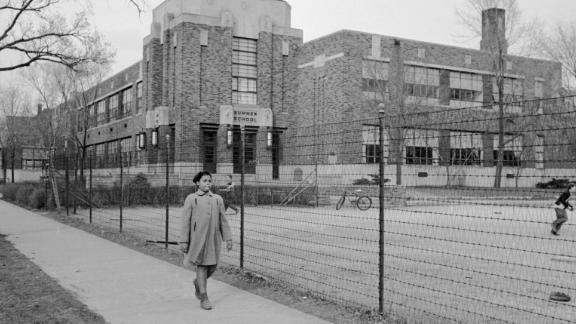 Linda Brown, 9, walks past Sumner Elementary School in Topeka, Kansas, in 1953. Her enrollment in the all-white school was blocked, leading her family to bring a lawsuit against the Topeka Board of Education. Four similar cases were combined with the Brown complaint and presented to the US Supreme Court as Brown v. Board of Education. The court