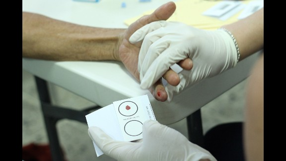 With a finger prick, the Argentine Forensic Anthropology Team takes a blood sample from family members in Honduras to extract DNA that will be matched against a database of forensic samples collected in Arizona.