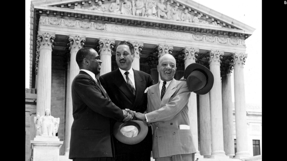 "From left, lawyers George E.C. Hayes, Thurgood Marshall and James M. Nabrit join hands outside the US Supreme Court on May 17, 1954, in celebration of the court's historic ruling. The ruling read in part: ""We conclude that, in the field of public education, the doctrine of 'separate but equal' has no place. Separate educational facilities are inherently unequal."""