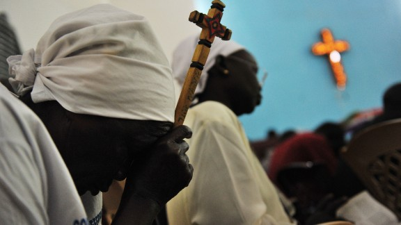 [File photo] A Sudanese woman holds a cross as she prays during Sunday service in a church in Juba on January 16, 2011.