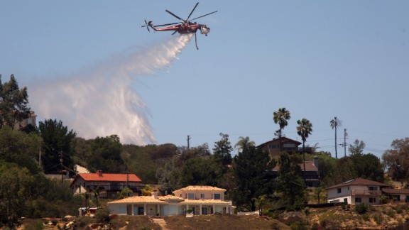 A helicopter drops water near homes in San Marcos, California, on May 16.