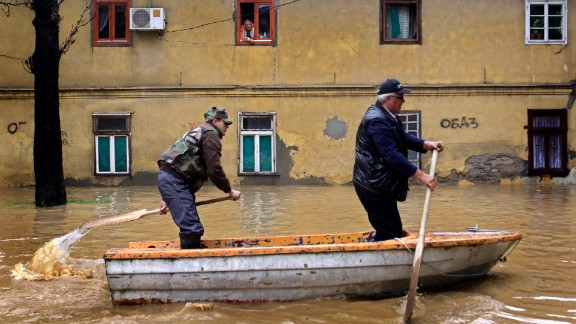 Men paddle through the flooded streets of Obrenovac on Friday, May 16. Authorities estimate that 90% of the town has been flooded.