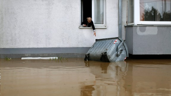 A woman tries to reach a trash container floating in the floodwaters in Obrenovac on May 16.