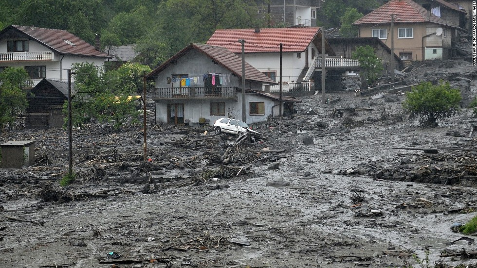 Landslide debris and floodwaters surround houses May 15 in the Bosnian village of Topcic Polje.