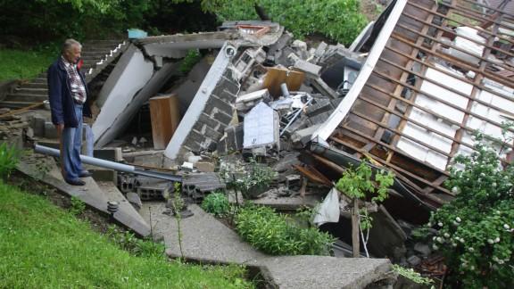 A man surveys the damage after a landslide near Sarajevo on May 15.