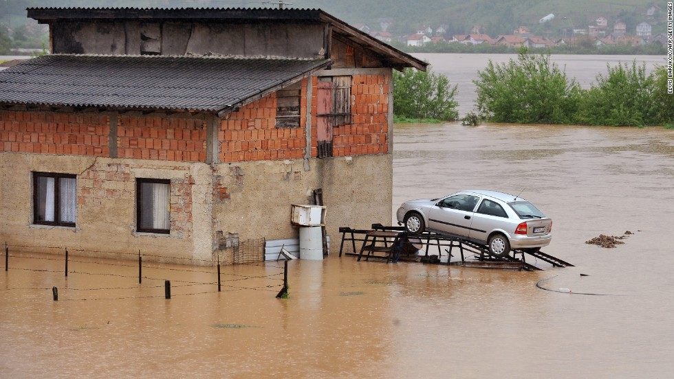 Floodwaters surround a car parked on a ramp Wednesday, May 14, in Doglodi, Bosnia-Herzegovina.