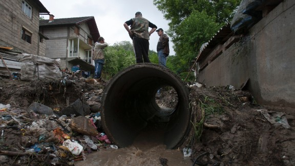 People work to clear debris from a small stream that was clogged and causing localized flooding near their homes in Tuzla, Bosnia-Herzegovina, on Sunday, May 12.