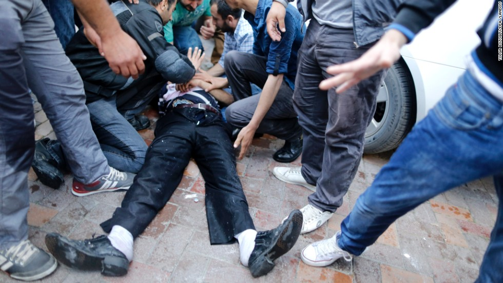 People try to help an injured man who was hit by the jet of a police water cannon on Friday, May 16, during a protest against the government after a mine explosion in Soma, Turkey.  Hundreds have taken to the streets across the country since nearly 300 miners died in a mine fire near Soma on May 13, protesting the government and a lack of safety regulations. Unions called for strikes May 15.