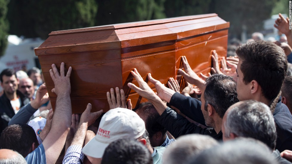 Mourners reach out to touch the coffin of a miner recovered from the Soma mine on May 17.