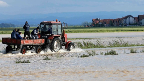 Residents ride in a wagon pulled by a tractor through a flooded field in the eastern Bosnian town of Bijeljina on May 17.