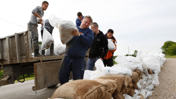 Residents place sandbags on a road near Orasje, Bosnia-Herzegovina, to protect the city from flooding on May 18.