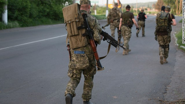 Pro-Russian militants walk to their positions to fight against Ukrainian government troops at a checkpoint blocking the major highway which links Kharkiv, outside Slovyansk, eastern Ukraine, Saturday, May 17, 2014.