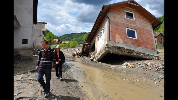 People walk past damaged houses in Krupanj on Sunday, May 18.