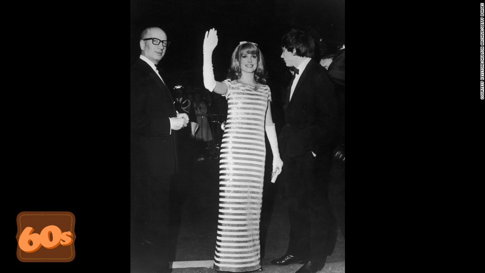 "French actress Catherine Deneuve greets her fans in white gloves and sequins at the 1966 Cannes Film Festival. She appeared in her 100th film ""Un conte de Noël"" in 2008 aged 64."