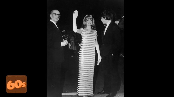 """French actress Catherine Deneuve greets her fans in white gloves and sequins at the 1966 Cannes Film Festival. She appeared in her 100th film """"Un conte de Noël"""" in 2008 aged 64."""