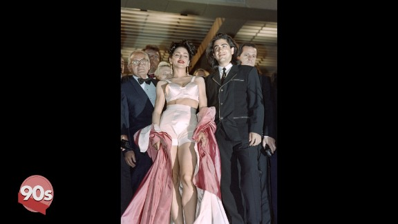 """The 90s saw a change in tack for red carpet attendees. Madonna kicked off the trend by wearing her Jean-Paul Gaultier underwear as outerwear at the screening of her movie """"In Bed with Madonna"""" in 1991. Director Alek Keshishian (left) looks on awkwardly."""