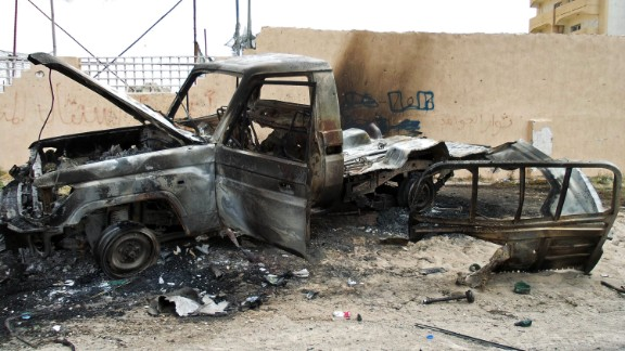A burnt out vehicle is seen on the side of the road leading to the airport in Tripoli on May 19, 2014 following attacks by armed groups the previous day.