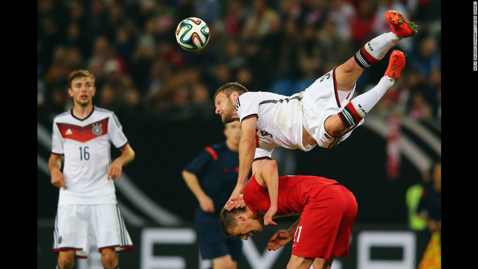 Shkodran Mustafi of Germany jumps over Arkadiusz Milik of Poland during an international match Tuesday, May 13, in Hamburg, Germany. The exhibition ended 0-0.