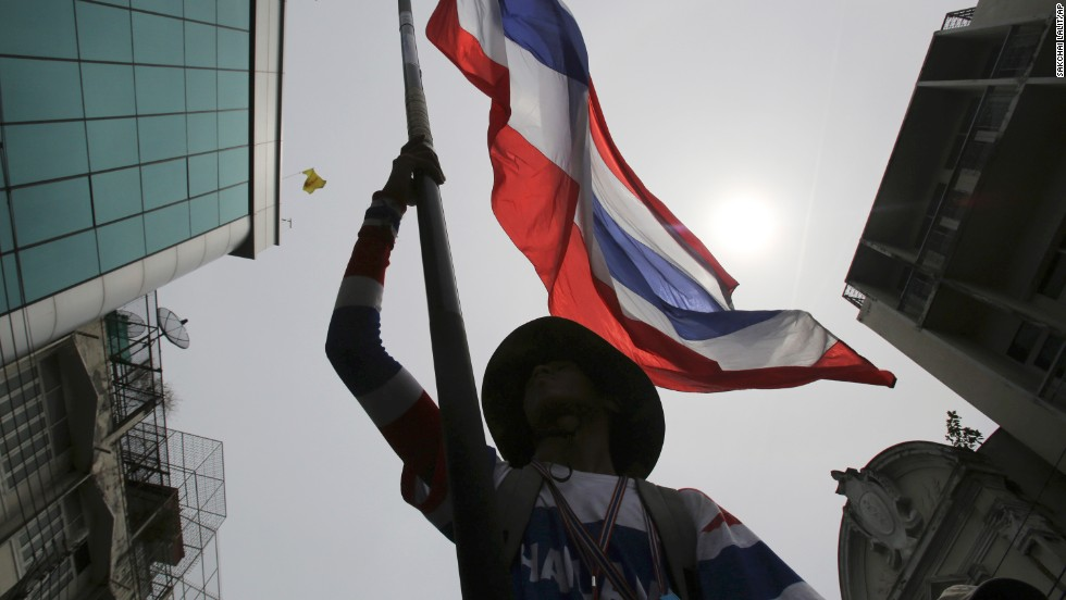 An anti-government protester waves a Thai national flag during a march through streets of Bangkok on Monday, May 19. Martial law went into effect at 3 a.m. the next morning.