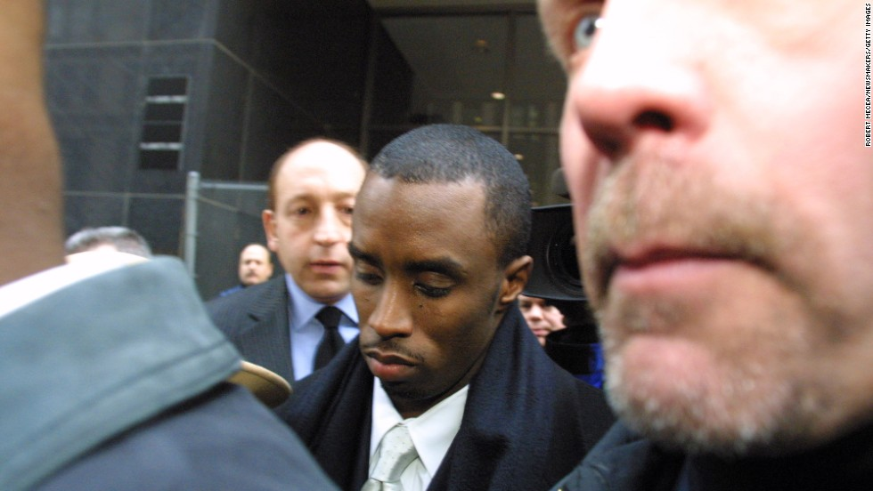 "Sean Combs, then known as ""Puffy,"" is flanked by security and court guards as he leaves the first day of his trial in January 2001 in New York. The rapper/producer was charged in connection with a 1999 shooting in a New York nightclub. He was found not guilty of all charges."