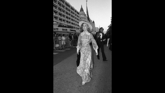 """French actress Brigitte Fossey arrives at the 1977 film festival in long checked dress with lace detailing and a provincial straw hat. Fossey was just five years old when she was cast by director René Clément to star in his film, """"Forbidden Games."""""""