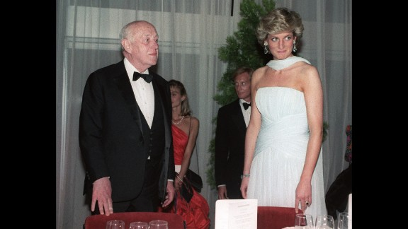 Princess Diana stands with British actor Alec Guinness in a demure blue dress and matching scarf at a Cannes gala dinner in 1987. The dress, by one of her favorite designers Catherine Walker, sold at auction for around $137, 000 in 2011.
