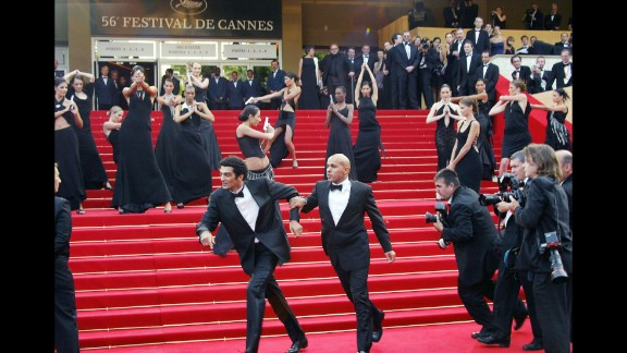 """Being chased by paparazzi and shot at by Bond girls is just another day in the life of french humorist duo Erik et Ramzy. The pair joke with the Bond girls upon arrival at the Palais des festivals before the screening of the film """"La Petite Lili"""" by French director Claude Miller during the Cannes film festival in 2003."""