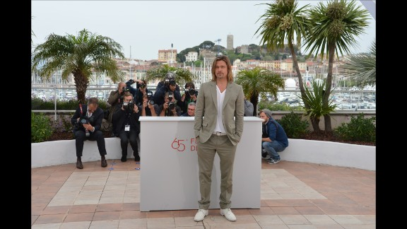 """It is not immediately clear why this long blonde hair and white lace up look works, but it really, really does. Brad Pitt works the photo call for """"Killing Me Softly"""" in Cannes, 2012."""