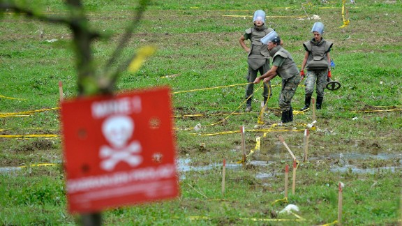 Bosnian soldiers repair land-mine warning signs in fields near the banks of the Bosnia River, which flooded near the town of Visoko, Bosnia-Herzegovina, on May 20.