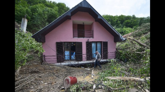 A man walks past a damaged house in Krupanj, Serbia, on May 20.