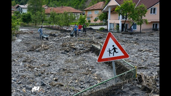 Residents clean streets of mud and rubble after a landslide in Topcic Polje, Bosnia-Herzegovina, on Tuesday, May 20.