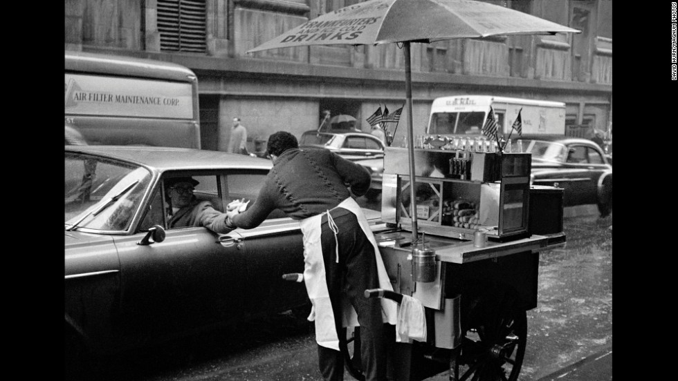 A man in New York buys a hot dog from his car window in Lower Manhattan in 1962.