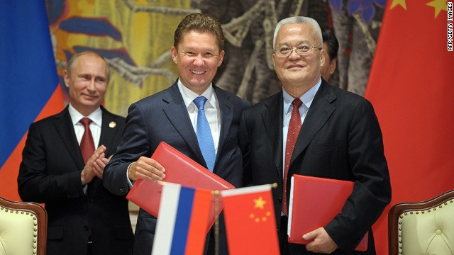 Russia's President Vladimir Putin (L) applauds during an agreement signing ceremony in Shanghai on May 21, 2014, with Gazprom CEO Alexei Miller (C) and Chinese state energy giant CNPC Chairman Zhou Jiping (R) attending the ceremony. China and Russia signed today a monumental, multi-decade gas supply contract in Shanghai, CNPC said, with reports saying it could be worth as much as $400 billion. AFP PHOTO / RIA-NOVOSTI / POOL ALEXEY DRUZHININALEXEY DRUZHININ/AFP/Getty Images