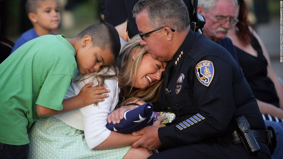Sergio Diaz, chief of the Riverside Police Department in Riverside, California, presents a flag to Regina Crain, the widow of slain police officer Michael Crain, during a memorial ceremony Monday, May 19. Michael Crain was among those killed by former Los Angeles police officer Christopher Dorner in February 2013, authorities said. At left providing comfort to Regina Crain is nephew Tyler Camonte.