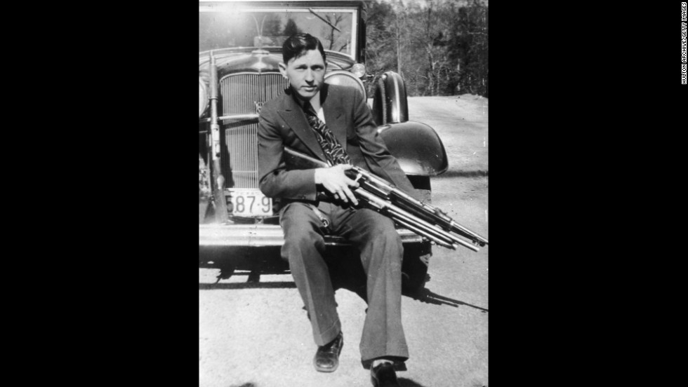 Barrow poses with two firearms on the bumper of a car. Barrow was sent to jail not long after he and Parker met in 1930. He escaped using a gun Parker smuggled to him. He was later recaptured, but he returned to his criminal life after being paroled in February 1932.