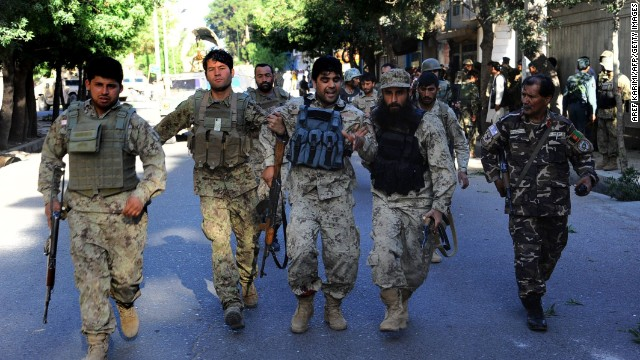 Afghan security forces assist an injured colleague at the scene of an attack on the Indian consulate in Herat on May 23.