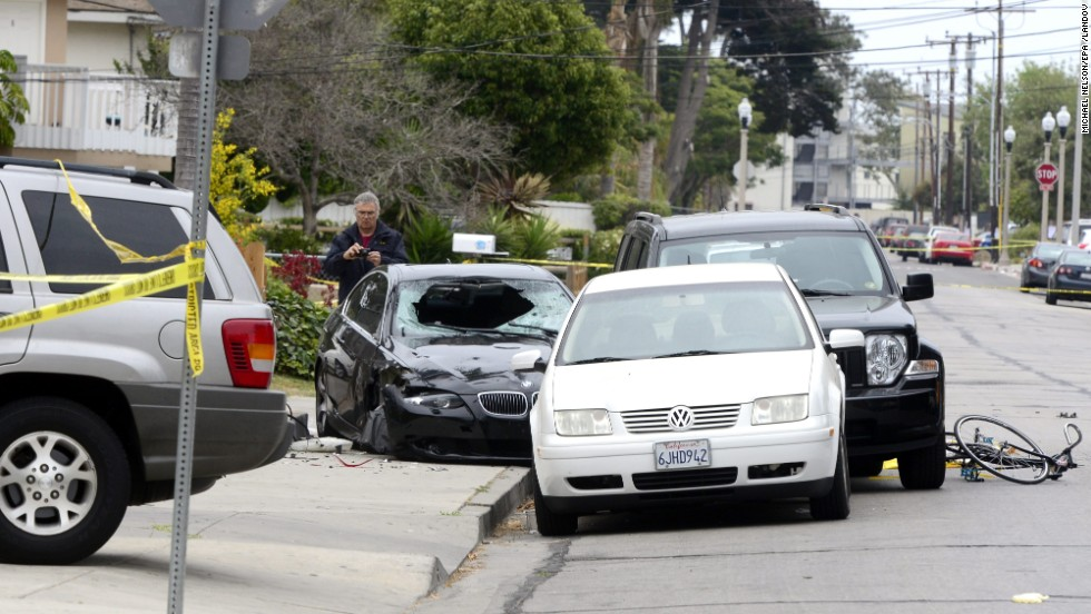 "A police officer inspects the gunman's car on May 24 after the killing spree in Isla Vista. The suspect, described as mentally disturbed and possibly bent on retribution, sprayed bullets from his car in a rampage called ""premeditated mass murder,"" Santa Barbara County sheriff's deputies said."