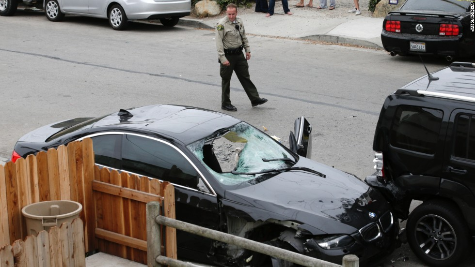 A Santa Barbara County deputy sheriff checks out the black BMW sedan driven by the suspected shooter. The gunman died from a gunshot wound after his car crashed, police said. It was unclear whether the fatal head wound was self-inflicted or the result of a firefight with police.